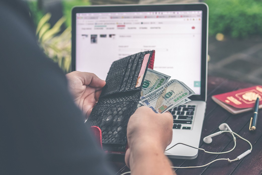 Man holding his wallet and counting money in front of a laptop screen.