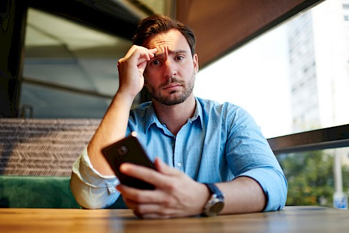 Man in blue shirt, frustrated, looking at phone