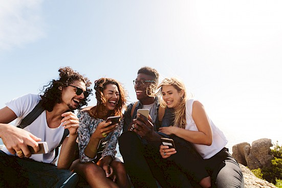 Friends holding smartphones laughing together