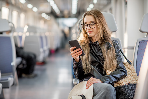 Woman browsing on her smartphone while traveling on a train